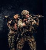 Δύο στρατιώτες ειδικών δυνάμεων στα πλήρη επιθετικά τουφέκια εκμετάλλευσης προστατευτικού εξοπλισμού και να στοχεύσει στους στόχο στοκ φωτογραφία