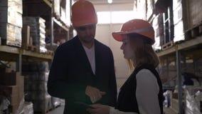 Δύο συνάδελφοι στα σκληρά κράνη στην αποθήκη εμπορευμάτων που συζητούν την εργασία με τα χέρια υπολογιστών και κουνημάτων ταμπλετ απόθεμα βίντεο
