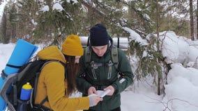 Δύο τουρίστες με τα σακίδια πλάτης, ένας νεαρός άνδρας και ένα κορίτσι, σε ένα χειμερινό χιονισμένο δάσος εξετάζουν έναν χάρτη εγ φιλμ μικρού μήκους