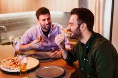 Δύο τύποι που τρώνε την πίτσα στο σπίτι στοκ φωτογραφία