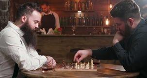 Δύο φίλοι με τις μοντέρνες γενειάδες που παίζουν ένα παιχνίδι σκακιού σε ένα μπαρ απόθεμα βίντεο