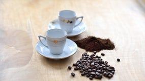 Δύο φλυτζάνια με τα φασόλια καφέ και το στηριγμένο καφέ στοκ φωτογραφία με δικαίωμα ελεύθερης χρήσης