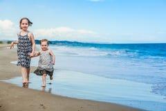 Δύο χαριτωμένες μικρές αδελφές που έχουν τη διασκέδαση σε μια παραλία στοκ φωτογραφία με δικαίωμα ελεύθερης χρήσης