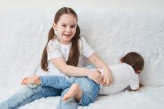 Δύο παιδιά, αδελφές κάθονται σε έναν άσπρο καναπέ στις άσπρα μπλούζες και το τζιν παντελόνι στοκ φωτογραφία