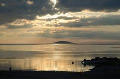 Île à distance au coucher du soleil Photos stock