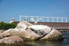 Île d'oiseau en pierre au milieu de la rivière dans la perspective d'un barrage Photographie stock