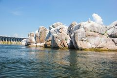 Île d'oiseau en pierre au milieu de la rivière dans la perspective d'un barrage Photographie stock libre de droits