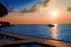 Île dans l'océan, villas d'overwater au coucher du soleil photos libres de droits