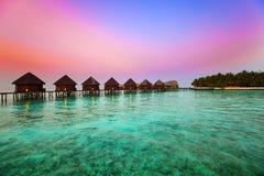 Île dans l'océan, villas d'overwater au coucher du soleil de temps images libres de droits