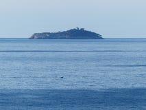Île dans la distance et un petit bateau de pêche Image stock