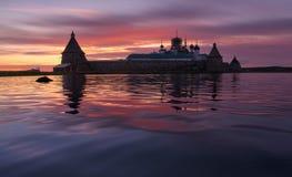 Île de Solovki, Russie Coucher du soleil rose fantastique au-dessus des vagues du lac saint avec la silhouette du monastère de So Photos stock