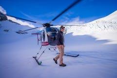 ÎLE DU SUD, LA NOUVELLE ZÉLANDE 24 MAI 2017 : Fermez-vous de l'hélicoptère et de l'attente pilote au-dessus de la neige des chass Photo libre de droits