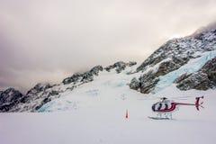 ÎLE DU SUD, LA NOUVELLE ZÉLANDE 24 MAI 2017 : Fermez-vous de l'hélicoptère rouge attendant au-dessus de la neige des chasseurs da Photos stock