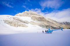 ÎLE DU SUD, LA NOUVELLE ZÉLANDE 24 MAI 2017 : Hélicoptère et pilote attendant au-dessus de la neige des chasseurs dans le ` du su Photographie stock