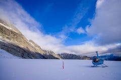 ÎLE DU SUD, LA NOUVELLE ZÉLANDE 24 MAI 2017 : Hélicoptère et pilote attendant au-dessus de la neige des chasseurs dans le ` du su Image stock