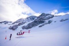 ÎLE DU SUD, LA NOUVELLE ZÉLANDE 24 MAI 2017 : Hélicoptère et pilote attendant au-dessus de la neige des chasseurs dans le ` du su Photographie stock libre de droits