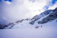 ÎLE DU SUD, LA NOUVELLE ZÉLANDE 24 MAI 2017 : Hélicoptère et pilote attendant au-dessus de la neige des chasseurs dans le ` du su Photo libre de droits