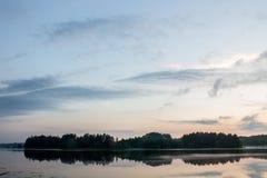 Île isolée au milieu du lac au coucher du soleil Photos stock