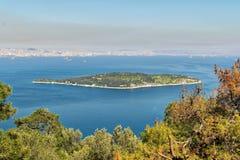 Île nacrée d'île de Sedef encadrée par les arbres verts de l'île de Buyukada Chacun des deux sont des voisinages dans le secteur  images libres de droits