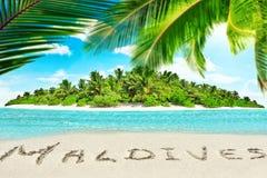 Île tropicale entière dans l'atoll dans l'océan et l'inscrip tropicaux image libre de droits