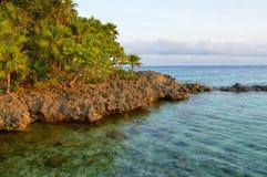 Île volcanique en mer entourée par les eaux clair comme de l'eau de roche Images stock