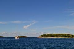 Îles vertes en mer azurée Un bateau dans la distance et le ciel bleu photos stock