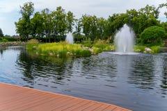 Îles vertes juteuses d'herbe au milieu de l'étang et de fontaines régénératrices à côté de elles photographie stock