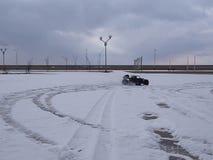Ραδιο-ελεγχόμενο αυτοκίνητο: ένα μικρό μαύρο με λάθη πρότυπο που ορμά με μια τρελλή ταχύτητα στο φρέσκο χιόνι απόθεμα βίντεο