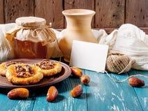 Ρομαντική ζωή πρωινού ακόμα, σε ένα αγροτικό ύφος με τα μπισκότα, το μέλι, τις ημερομηνίες, την κανάτα γάλακτος και την κάρτα στοκ εικόνα με δικαίωμα ελεύθερης χρήσης