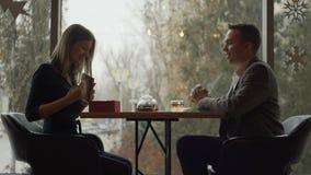 Ρομαντικός φίλος που δίνει το δώρο στη χαμογελώντας φίλη του σε reastaurant απόθεμα βίντεο