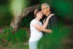 Ρομαντικός περίπατος μέσω των ξύλων Ανώτερο ζεύγος που περπατά μαζί σε ένα δάσος, κινηματογράφηση σε πρώτο πλάνο στοκ φωτογραφία