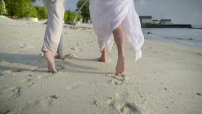 Ρομαντικό ταξίδι, νέο ζεύγος με τα γυμνά πόδια που τρέχουν κατά μήκος της υγρής άμμου κατά τη διάρκεια διακοπών πολυτέλειας απόθεμα βίντεο