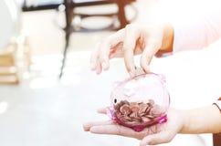 Ρόδινο βάζο νομισμάτων υπό εξέταση στοκ φωτογραφίες