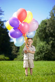 �hild with a bunch of balloons in their hands Royalty Free Stock Image