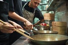 Όλα πρέπει να είναι τέλεια Αρχιμάγειρας εστιατορίων που φαίνεται οι βοηθοί του που μαγειρεύουν ένα νέο πιάτο σε μια κουζίνα στοκ φωτογραφία