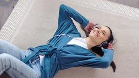 Όμορφα ακουστικά εκμετάλλευσης μουσικής ακούσματος κοριτσιών χαμόγελου τοπ άποψης με το χέρι που βρίσκονται στο πάτωμα φιλμ μικρού μήκους