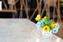 Όμορφα λουλούδια σε ένα άσπρο ποδήλατο στον ξύλινο πίνακα Όμορφα λουλούδια στο άσπρο ποδήλατο στον ξύλινο πίνακα στοκ εικόνες