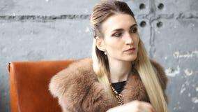 Όμορφη γοητευτική γυναίκα στην τοποθέτηση παλτών γουνών στο στούντιο φιλμ μικρού μήκους