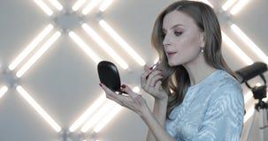 Όμορφη γυναίκα με την κατσαρωμένη τρίχα που εξετάζει τα χείλια καθρεφτών και ζωγραφικής από την ερμηνεία φιλμ μικρού μήκους