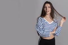 Όμορφη γυναίκα με τη χνουδωτή τρίχα, που ντύνεται άνετα ενάντια σε έναν γκρίζο τοίχο στούντιο στοκ φωτογραφίες