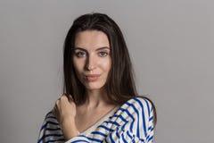 Όμορφη γυναίκα με τη χνουδωτή τρίχα, που ντύνεται άνετα ενάντια σε έναν γκρίζο τοίχο στούντιο στοκ εικόνα με δικαίωμα ελεύθερης χρήσης