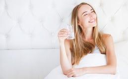 Όμορφη γυναίκα που απολαμβάνει ένα ποτήρι του νερού στην κρεβατοκάμαρα το πρωί στοκ φωτογραφίες