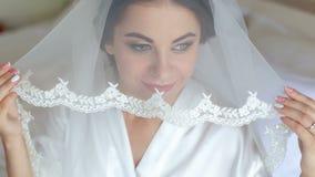 Όμορφη γυναίκα που παίρνει έτοιμη για τη ημέρα γάμου, το κράτημα του πέπλου και το χαμόγελο απόθεμα βίντεο