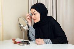 Όμορφη μουσουλμανική γυναίκα που εφαρμόζει mascara Νέα αραβική γυναίκα που χρησιμοποιεί τη βούρτσα μαστιγίων στοκ φωτογραφία με δικαίωμα ελεύθερης χρήσης