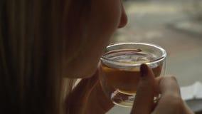 Όμορφη νέα γυναίκα που απολαμβάνει το τσάι Γυναίκα που φυσά σε ένα καυτό τσάι απόθεμα βίντεο