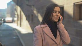 Όμορφη νέα κυρία που μιλά στο τηλέφωνο, περπατώντας στην αρχαία πόλη στο κέντρο της πόλης, περιπλάνηση απόθεμα βίντεο