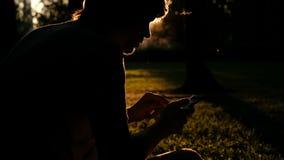Όμορφη σκιαγραφία ενός ατόμου με ένα smartphone στα χέρια του στο ηλιοβασίλεμα Χαλαρώστε, έννοια φύσης απόθεμα βίντεο