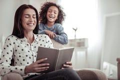 Όμορφη συμπαθητική μητέρα που διαβάζει ένα βιβλίο μαζί με μια κόρη στοκ φωτογραφίες