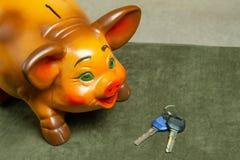 Όμορφη piggy τράπεζα στα κλειδιά ενός πράσινου υποβάθρου και σπιτιών στοκ εικόνα με δικαίωμα ελεύθερης χρήσης