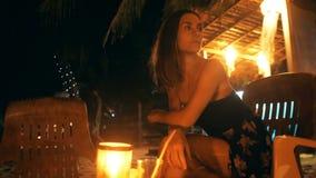 Όμορφος ευτυχής θηλυκός τουρίστας στην καρέκλα φραγμών σαλονιών παραλιών νύχτας που κοιτάζει γύρω από την αναμονή κάποιο στο θέρε απόθεμα βίντεο